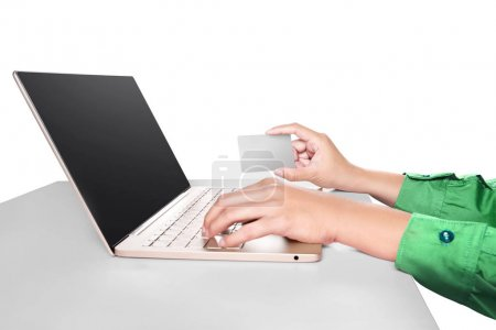 Hands typing on laptop while holding credit card on desk