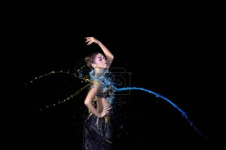 Young asian belly dancer in motion with colorful paint on black background