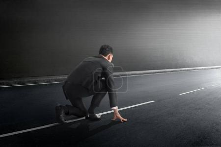 Attractive asian businessman in ready position to run on tunnel