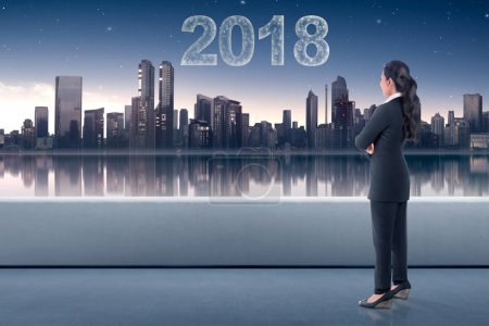 Young asian business woman looking at the city with star make 2018 shape on the sky