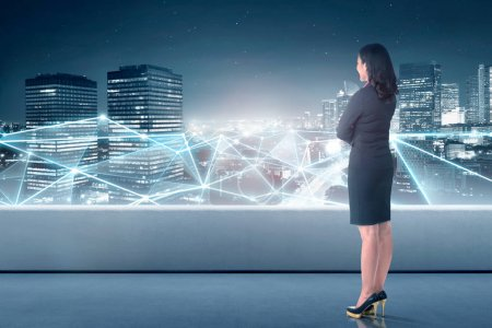 Beautiful asian business woman looking at network connection on the cityscape background