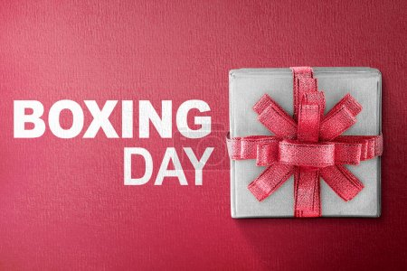 White gift box tied with red ribbon with Boxing Day text on red background