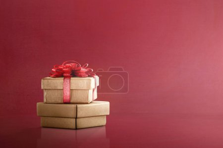 Golden gift boxes with red ribbon on red background. Boxing Day Concept