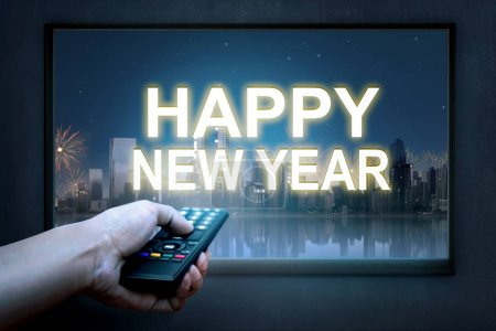 Hand holding tv remote control with new year sign on TV screen. Happy New Year 2018