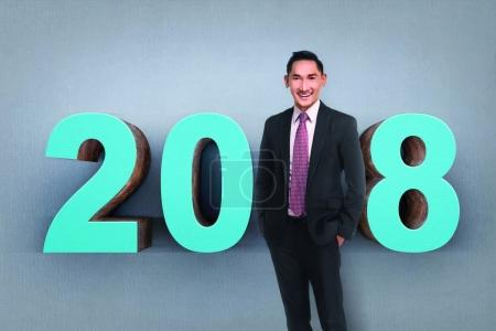 Handsome asian businessman stand as a part of number 2018 with grey wall background. Happy New Year 2018
