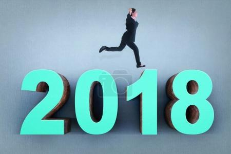 Young asian business woman running above number 2018 with grey wall background. Happy New Year 2018