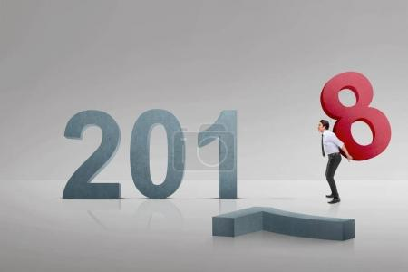 Young asian businessman carrying number 8 to make number 2018. Happy New Year 2018