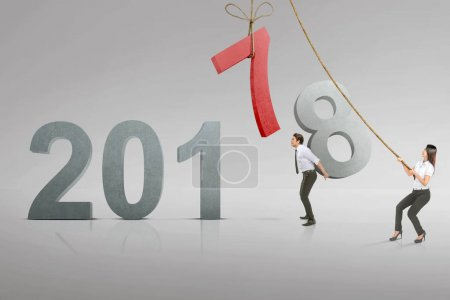 Asian business team replace number 7 with 8 to fill 2018. Happy New Year 2018