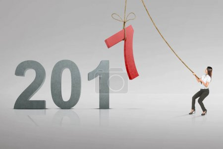 Attravtice asian businesswoman pulling number 7 with rope to be changed to 2018. Happy New Year 2018