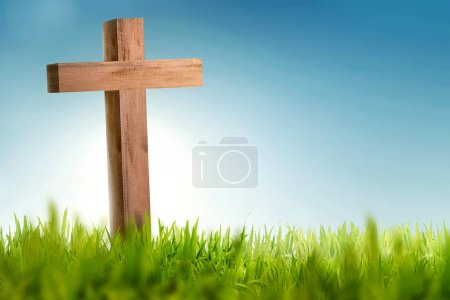 Wooden christian cross on green grass with blue sky background