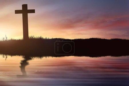 Photo pour Silhouette de croix chrétienne sur le terrain avec flou reflet dans l'eau du lac au coucher du soleil - image libre de droit