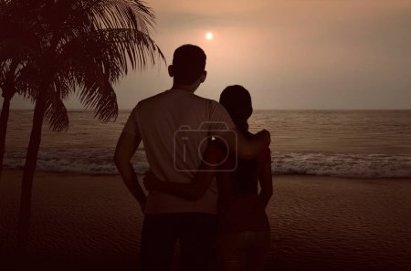 Silhouette of asian couple hugging and enjoying sunset together on the beach