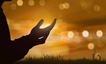 Silhouettes of human hands with open palms praying to god at sunset background