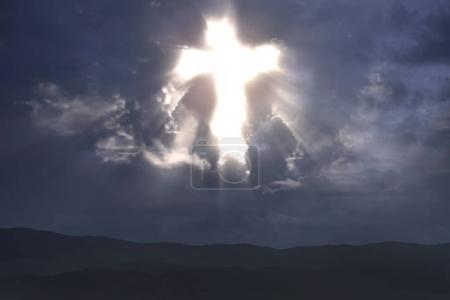 Rays of light from Christian cross on sky