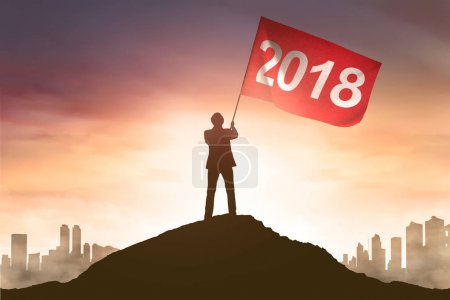 businessman hold a red flag with 2018 number