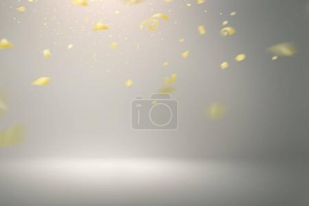 Falling gold confetti on grey background