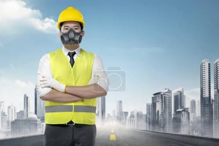 Handsome asian worker in a reflective vest standing on the urban road