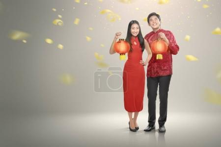 Happy chinese couple in cheongsam clothes holding red lanterns with confetti background, Happy Chinese New Year concept