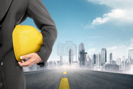 Construction worker holding yellow helmet on city background