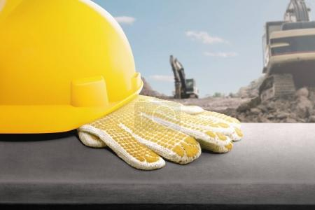 yellow helmet and gloves on desk at construction site