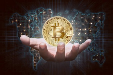 male hand showing golden bitcoin as virtual money on digital world map background