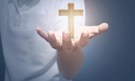 wooden cross above human hand over blur background