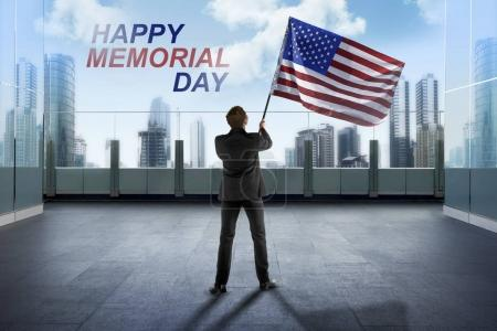 Businessman waving American flag for happy memorial day with blue sky background