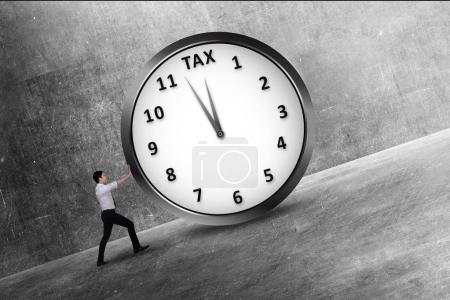 Handsome asian businessman pushing on the clock with tax message. Goods and Services Tax concept.