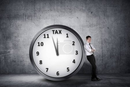 Happy asian businessman lean back on the clock with deadline time for paying tax. Goods and Services Tax concept.