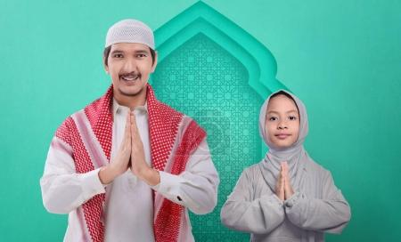 Portrait of asian muslim family praying together o...