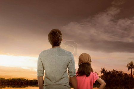 Portrait of father and daughter enjoying sunset view with dramatic sky background
