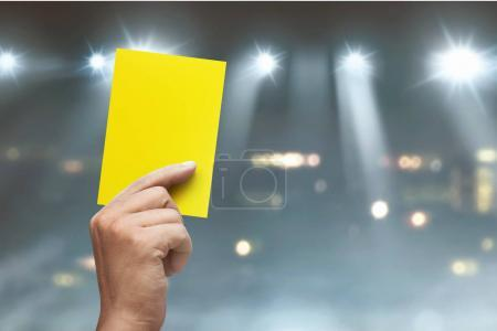 Hand of referee with yellow card on soccer stadium at match