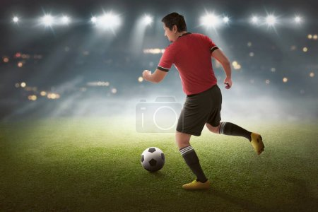 Young asian soccer player with the ball on the stadium