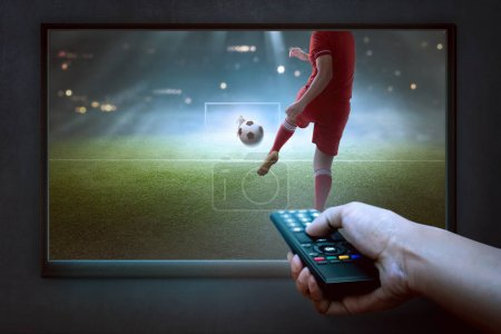 People hands with remote watching football game on the tv