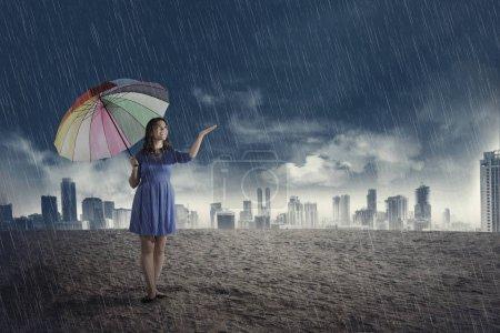Happy asian woman with umbrella when rain over dark sky background