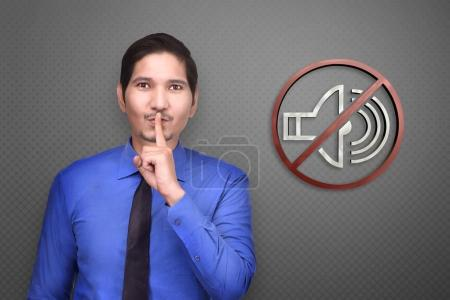 Young asian businessman with silence gesture and asking for quiet on gray background