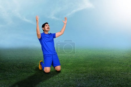 Handsome asian soccer player celebrate his goal on stadium field