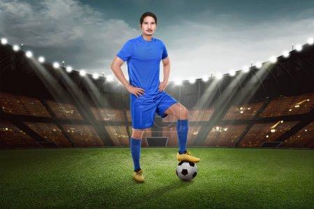 Attractive asian footballer with ball on the stadium field