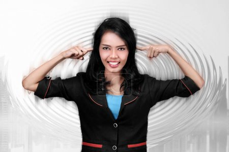 Young asian business woman closing ears over abstract background
