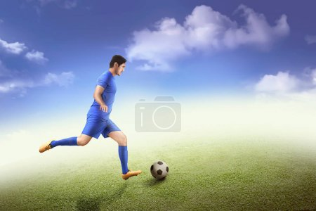 Side view of asian footballer kicking ball on field