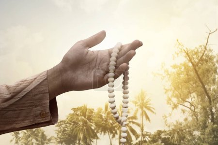 Photo for Muslim man holding prayer beads with sunset background - Royalty Free Image