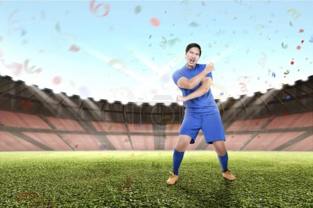 Young asian football player celebrate the champion at stadium