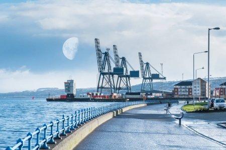 Photo pour L'esplanade de Greenock à l'extrémité ouest de la ville surplombant le terminal de ClydePort avec son port et ses grues lourdes. Demi-lune tôt le matin et neige sur les collines Greenock - image libre de droit