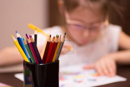 a girl draws with colored pencils