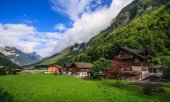 Beautiful panoramic postcard view of picturesque rural mountain scenery in the Alps with traditional old alpine mountain chalets and fresh green meadows on a sunny day with blue sky and clouds in the summer.