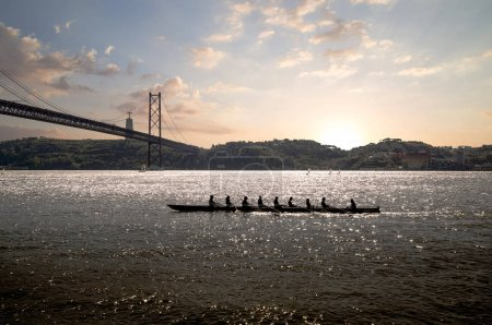 silhouette of people on rowing boat on the sea with suspension bridge in the background at sunset. Lisbon, Portugal.