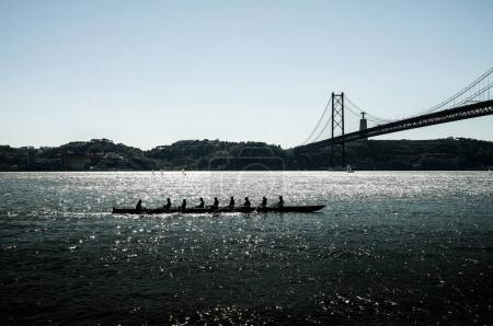 silhouette of people on rowing boat on the sea with suspension bridge in the background. Lisbon, Portugal.