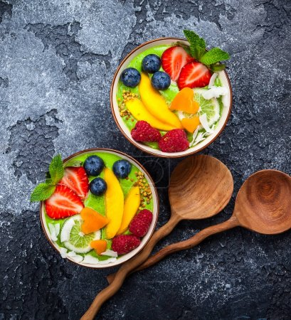 Green smoothie in bowl on black