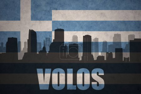 abstract silhouette of the city with text Volos at the vintage greece flag