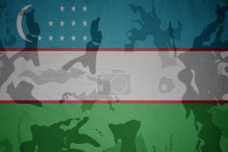 Photo pour Drapeau de l'Ouzbékistan sur le fond de texture kaki. concept militaire - image libre de droit